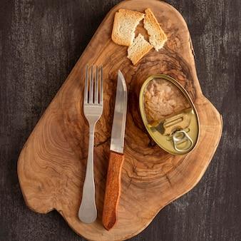 Vista superior da lata de atum em uma placa de madeira com talheres