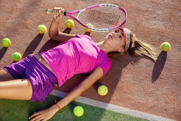 Vista superior da linda garota na tampa deitado na quadra de tênis ao ar livre com uma raquete na mão e um monte de bolas no chão após o treino.