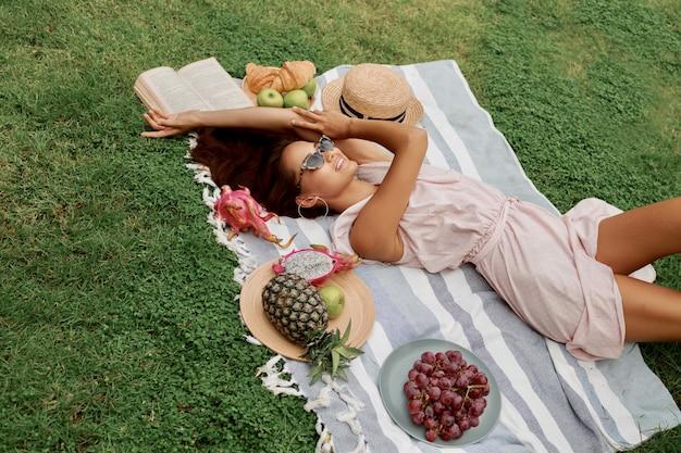 Vista superior da linda mulher romântica no vestido deitado na grama verde.