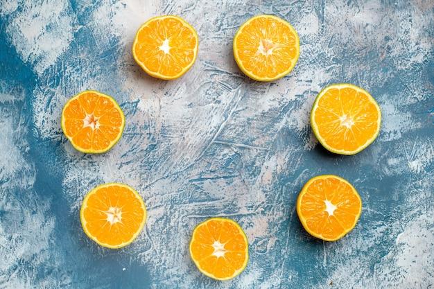 Vista superior da linha do círculo cortada laranjas na mesa branca azul