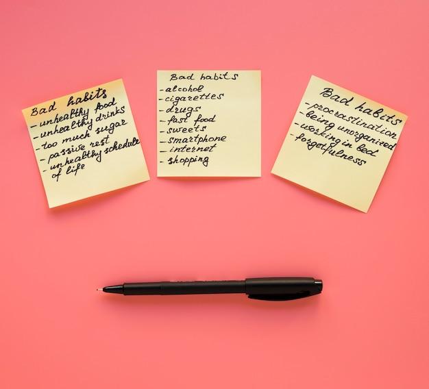Vista superior da lista de maus hábitos em notas autoadesivas