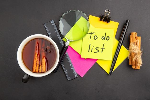 Vista superior da lista de tarefas escrita em nota adesiva amarela notas adesivas coloridas caneta lupa paus de canela régua xícara de chá