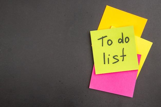 Vista superior da lista de tarefas escrita em nota adesiva verde notas adesivas coloridas no escuro com local de cópia