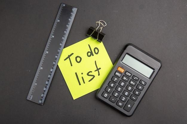 Vista superior da lista de tarefas escrita na calculadora da régua de notas adesivas no escuro
