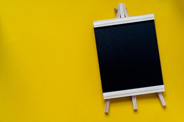Vista superior da lousa preta em branco sobre fundo amarelo para o conceito de design