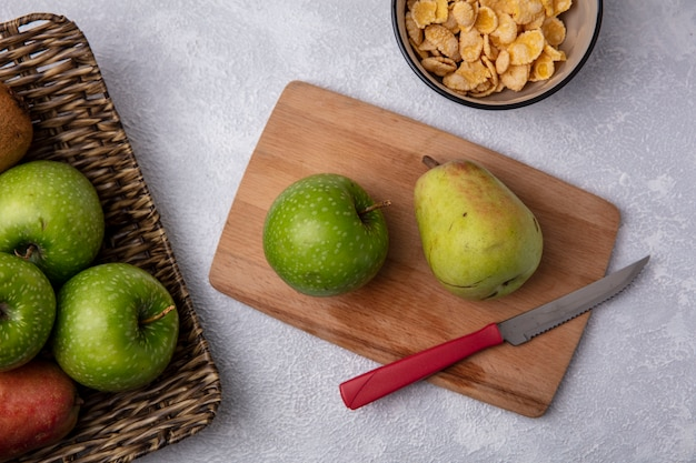 Vista superior da maçã verde com pêra e faca na tábua com flocos de milho em uma tigela no fundo branco