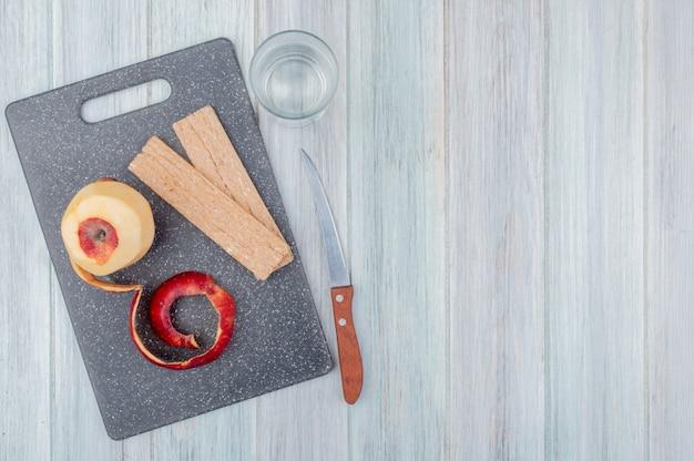 Vista superior da maçã vermelha com casca e biscoitos na tábua com faca e copo de água na mesa de madeira com espaço de cópia