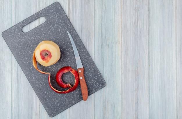 Vista superior da maçã vermelha com casca e faca na tábua sobre fundo de madeira com espaço de cópia