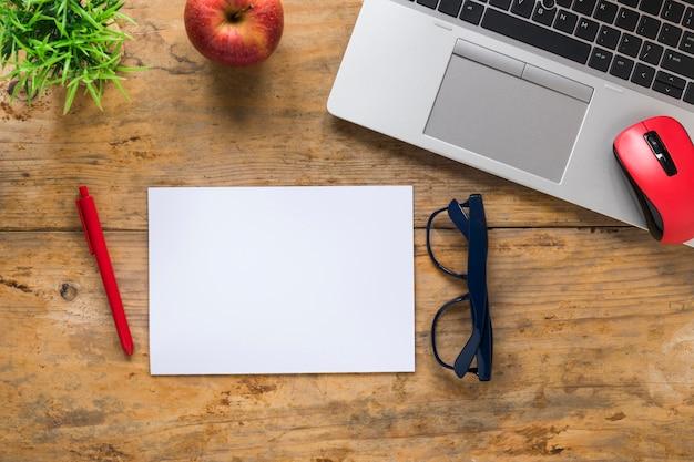 Vista superior da maçã vermelha; rato; computador portátil; caneta; óculos e papel branco em branco na mesa de madeira
