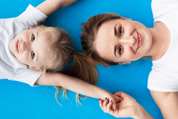 Vista superior da mãe feliz posando com a filha no tapete de ioga