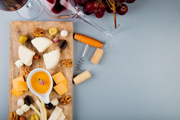 Vista superior da manteiga com queijo uva nozes na placa de corte e saca-rolhas rolhas em branco com espaço de cópia