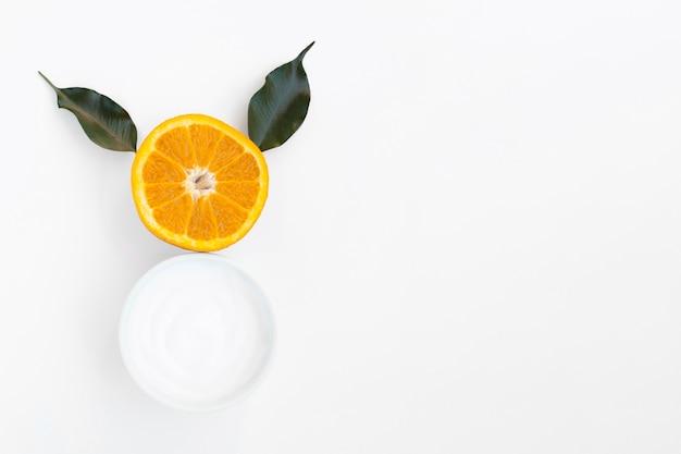 Vista superior da manteiga corporal e laranja em fundo branco