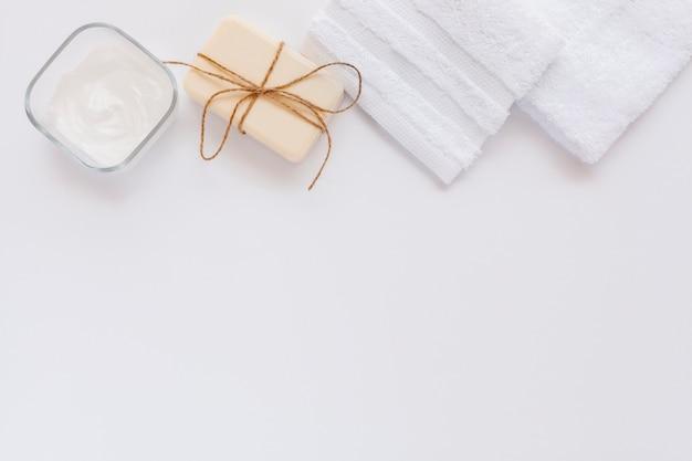 Vista superior da manteiga corporal e sabão no bakground simples com espaço de cópia