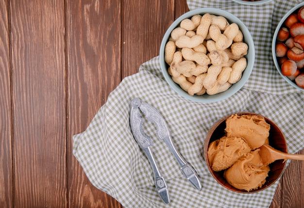 Vista superior da manteiga de amendoim em uma tigela de madeira com avelãs e amendoins com casca em tigelas e biscoito de nozes na toalha de mesa xadrez em fundo xadrez de madeira com fundo de cópia