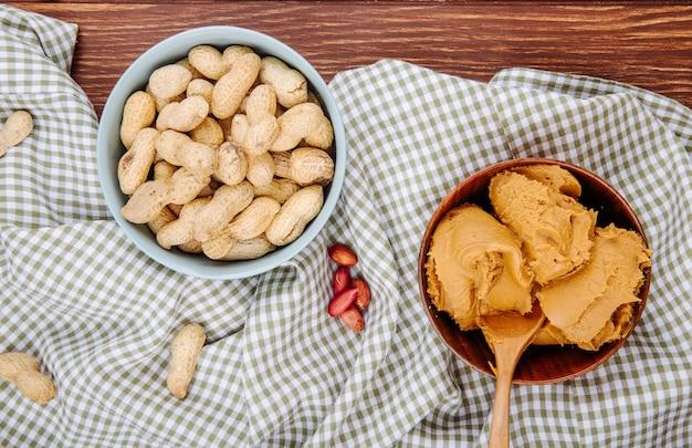 Vista superior da manteiga de amendoim em uma tigela de madeira com uma tigela cheia de amendoins em fundo de madeira