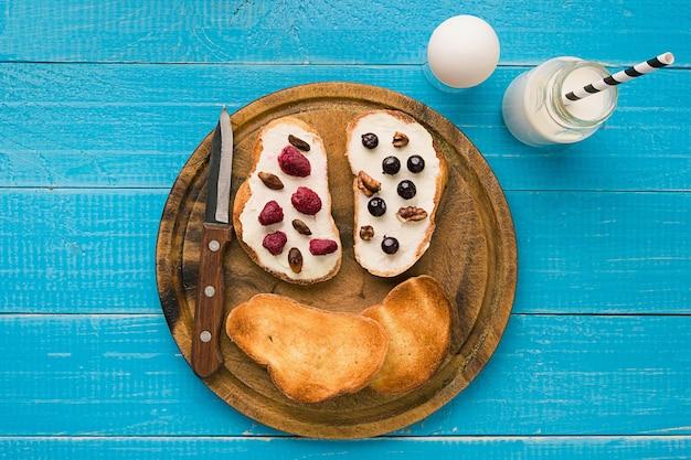 Vista superior da manteiga e das frutas vermelhas do pão torrado. copie o espaço
