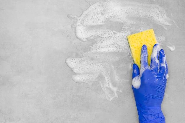 Vista superior da mão com luva cirúrgica, limpeza de superfície com esponja