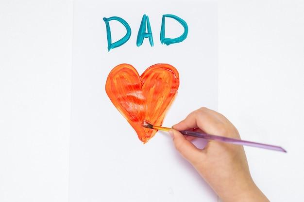 Vista superior da mão da criança desenhando um coração vermelho com a palavra pai cartão por aquarelas em papel branco. dia dos pais e o conceito de família.
