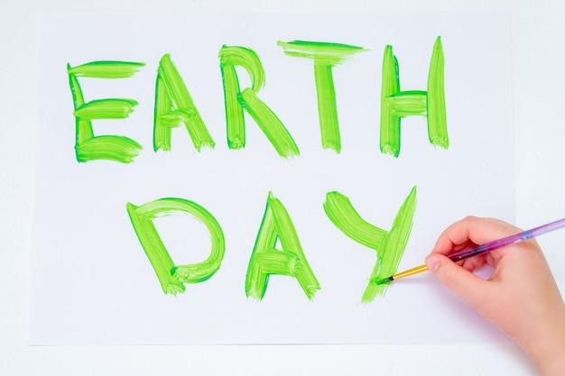 Vista superior da mão da criança escrevendo palavras do dia da terra com pincel por aquarela verde em papel branco. conceito de dia da terra.