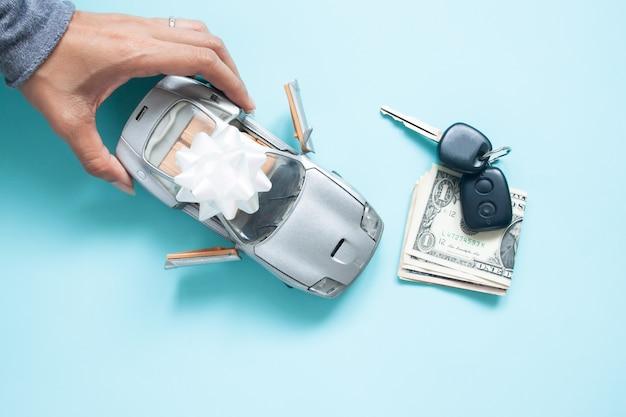 Vista superior da mão da mulher com o carro, chave e dinheiro no fundo da cor azul