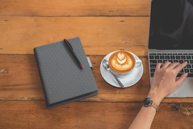 Vista superior da mão da mulher usando o computador portátil com notebook e xícara de café