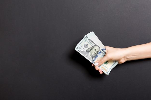 Vista superior da mão dando notas de cem dólares