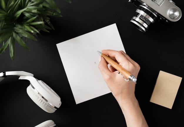 Vista superior da mão de um estudante leigo escreve uma nota com uma caneta em uma folha de papel branca ao lado da câmera de filme com fones de ouvido e papel de nota em uma mesa preta