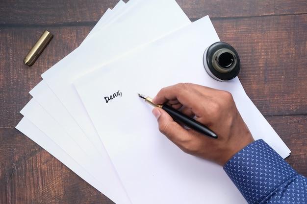 Vista superior da mão de um homem escrevendo uma carta com caneta-tinteiro