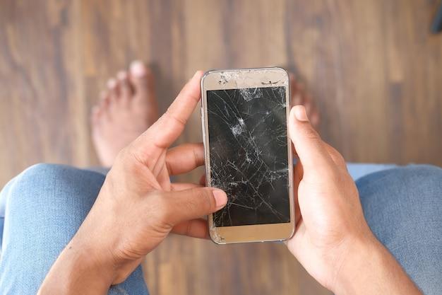 Vista superior da mão de um homem segurando um telefone inteligente quebrado