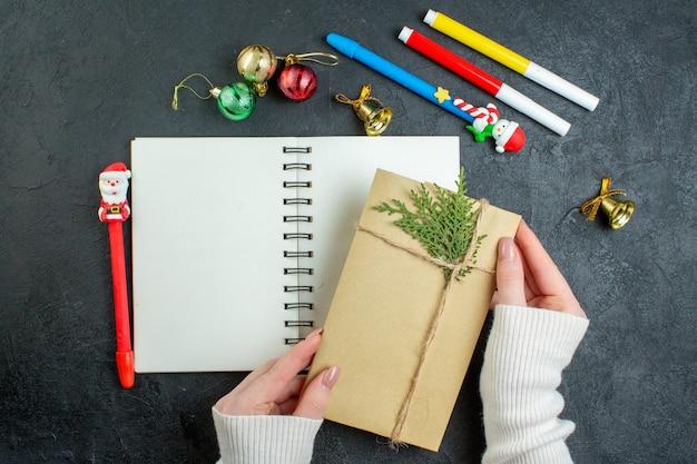 Vista superior da mão de um presente no caderno espiral com acessórios de decoração de escrita de feliz ano novo em fundo preto