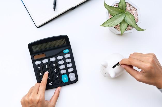 Vista superior da mão de uma mulher colocando moedas no cofrinho enquanto usa a calculadora na mesa branca em casa.