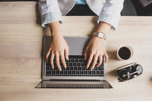 Vista superior da mão de uma mulher digitando no teclado de um laptop em uma mesa de escritório de madeira