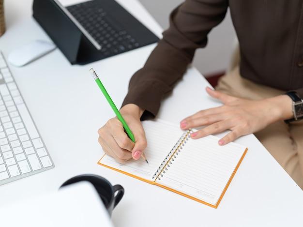 Vista superior da mão de uma trabalhadora de escritório escrevendo em um caderno em branco na mesa do computador