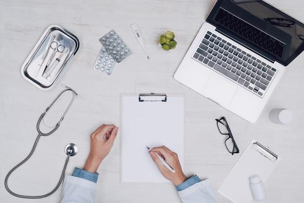 Vista superior da mão do médico de medicina trabalhando na mesa.