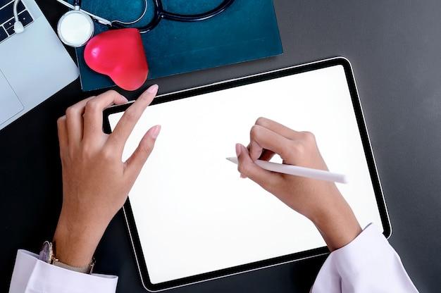 Vista superior da mão do médico escrevendo na tela do tablet enquanto está sentado na mesa.