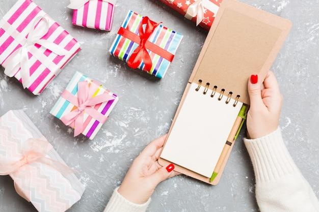 Vista superior da mão feminina, abrindo um notebook em cimento natal