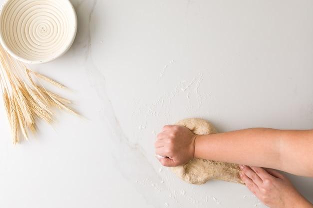 Vista superior da mão feminina, amassar massa de pão em uma mesa de mármore com uma tigela de pão vazia e trigo com espaço para texto