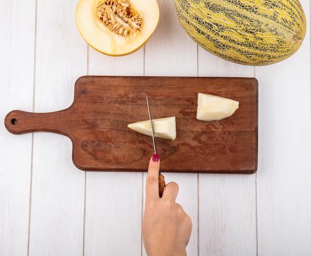 Vista superior da mão feminina cortando o melão em fatias com a faca na placa de madeira da cozinha na madeira branca