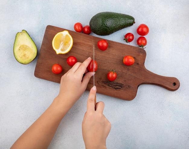 Vista superior da mão feminina cortando tomates em fatias na mesa da cozinha com uma faca com abacate e limão