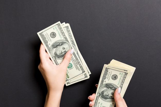 Vista superior da mão feminina, dando algum dinheiro