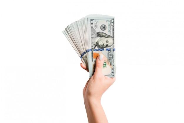 Vista superior da mão feminina isolada, segurando um leque de notas de cem dólares. riqueza e conceito rico