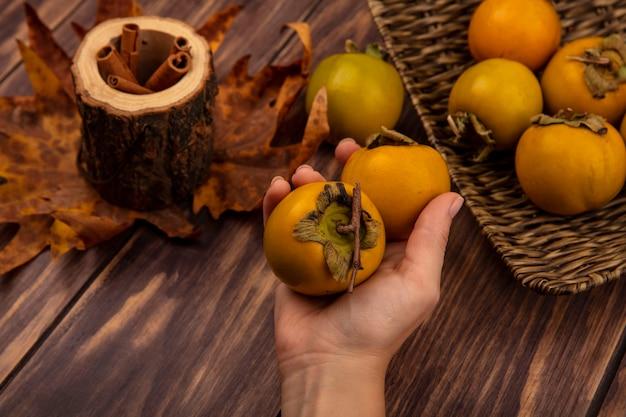 Vista superior da mão feminina segurando frutas frescas de caqui com paus de canela em uma jarra de madeira com folhas em uma mesa de madeira