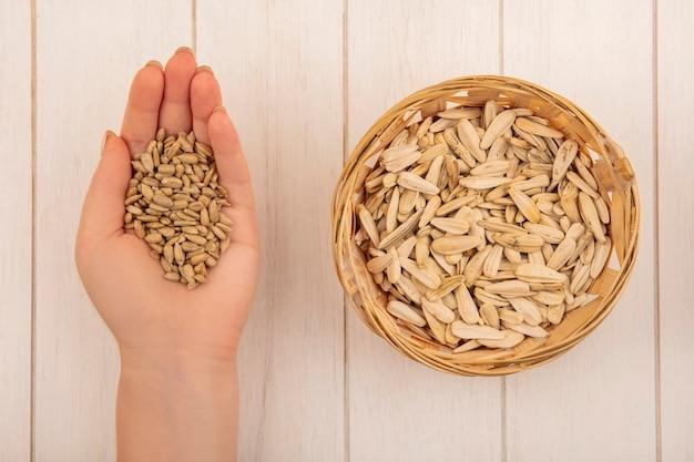 Vista superior da mão feminina segurando saborosas sementes de girassol com casca salgada e sementes de girassol brancas em um balde sobre uma mesa de madeira bege