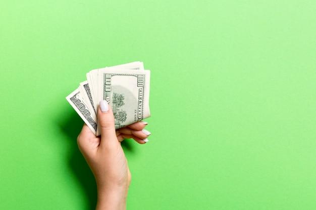 Vista superior da mão feminina segurando um maço de dinheiro em fundo colorido. cem dólares. conceito de negócio com espaço vazio para seu projeto. conceito de caridade e dicas
