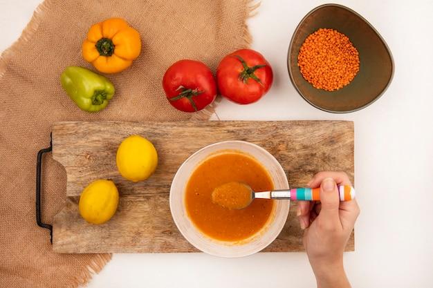 Vista superior da mão feminina segurando uma colher com sopa de lentilha fresca em uma tigela sobre uma placa de cozinha de madeira em um pano de saco com pimentas coloridas e tomates isolados em uma parede branca