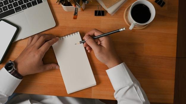 Vista superior da mão masculina escrevendo em um caderno em branco na mesa de trabalho de madeira no escritório doméstico