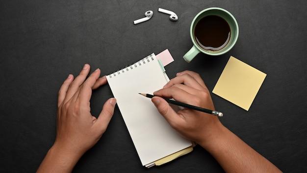 Vista superior da mão masculina escrevendo no caderno com a caneca de café e suprimentos na mesa preta