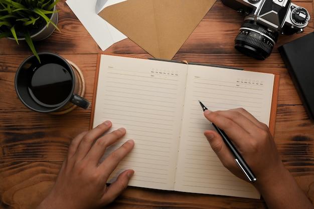 Vista superior da mão masculina escrevendo no caderno em branco na mesa de madeira com a câmera e a xícara de café