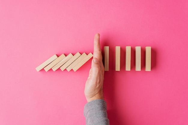 Vista superior da mão masculina, interrompendo o dominó em colapso