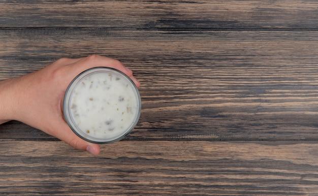 Vista superior da mão masculina segurando o copo de sopa de iogurte em fundo de madeira com espaço de cópia